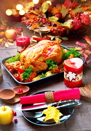 table: Thanksgiving dinner table served with turkey, decorated with bright autumn leaves