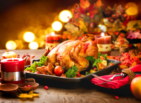 baked chicken: Thanksgiving dinner table served with turkey, decorated with bright autumn leaves