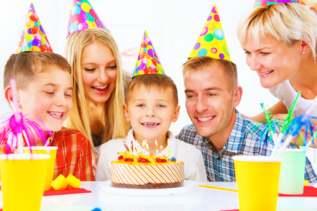 Birthday. Little boy blows out candles on birthday cake at party photo