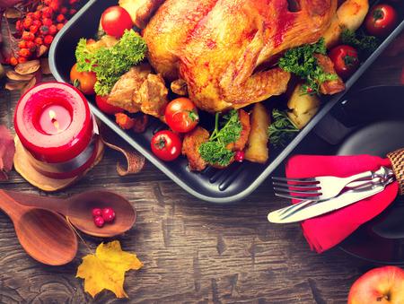 natale: Tavolo da pranzo del Ringraziamento servito con tacchino, decorato con foglie autunnali