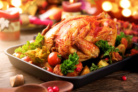 oven: Roasted turkey garnished with potato, vegetables and cranberries. Thanksgiving or Christmas dinner