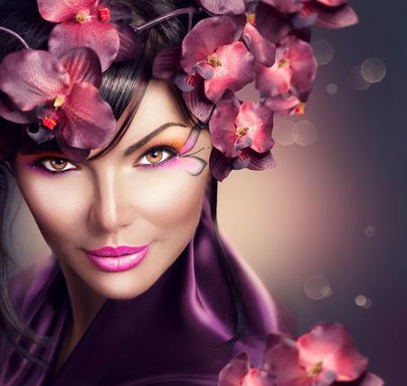Mooie vrouw met orchidee bloem kapsel en creatieve make-up Stockfoto