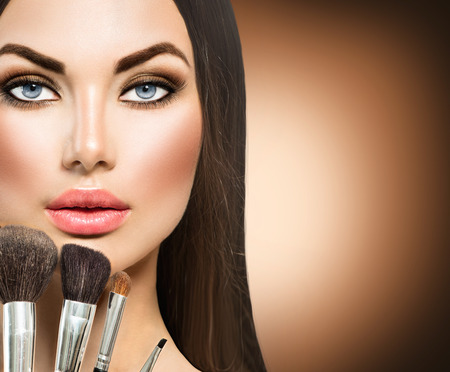 apply: Beauty brunette girl with makeup brushes
