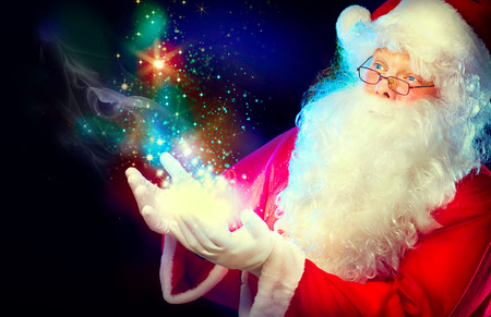 make a gift: Santa Claus with magic gift in his hands Stock Photo