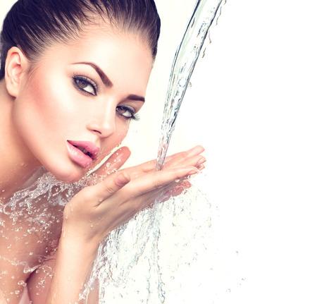 schoonheid: Mooie model vrouw met spatten van water in haar handen Stockfoto