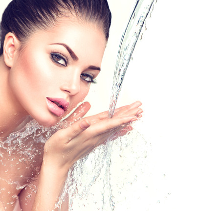 belleza: Mujer modelo hermosa con salpicaduras de agua en sus manos