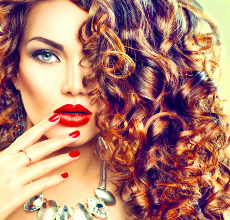 cabello: Mujer joven de la belleza morena con el pelo rizado, maquillaje perfecto y manicura
