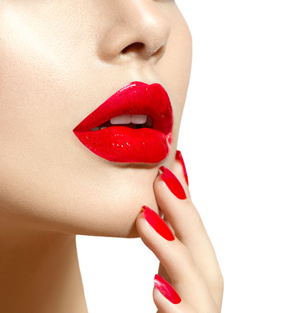 up: Beauty model girl with red sexy lips and nails closeup. Manicure and makeup