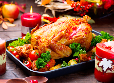 Roasted turkey garnished with potato, vegetables and cranberries. Thanksgiving or Christmas dinner