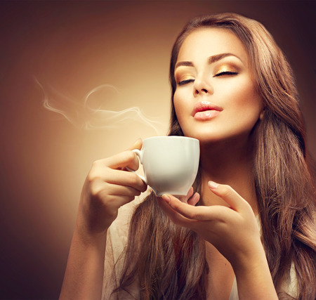 Beautiful young woman enjoying hot coffee