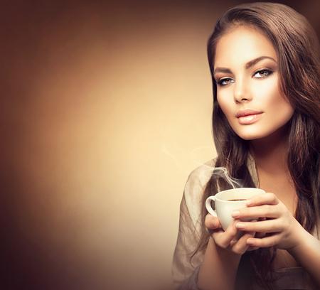 taza de té: Joven y bella mujer beber café caliente