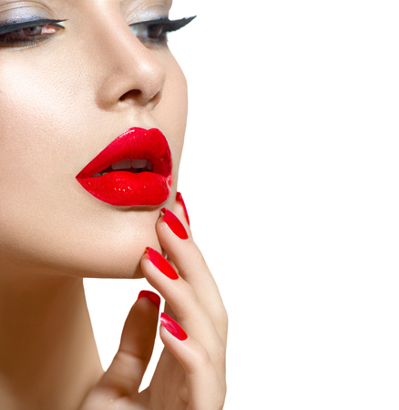 Beauty model girl with red sexy lips and nails closeup. Manicure and makeup
