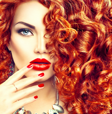 hairdressing: Beauty young woman with curly red hair, perfect makeup and manicure