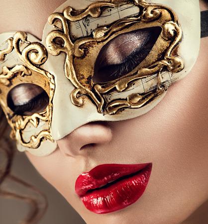 lipgloss: Beauty model woman wearing venetian masquerade carnival mask at party