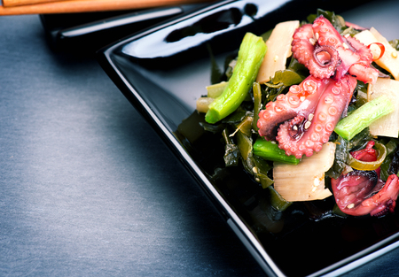 black octopus: Japanese salad with octopus and ginger. Seafood over black background Stock Photo