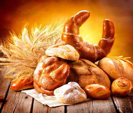 sheaf: Various bread and sheaf of wheat ears on a wooden table