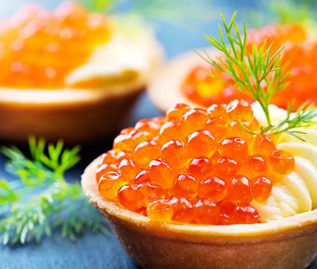 comida gourmet: Tartlets with red caviar closeup. Gourmet food