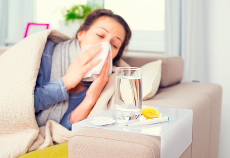 Gripe. Mujer enferma estornudos en el tejido Foto de archivo