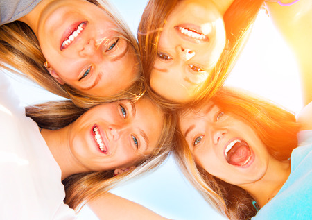 smiling teenagers: Girlfriends staying together, looking at camera and laughing over blue sky Stock Photo