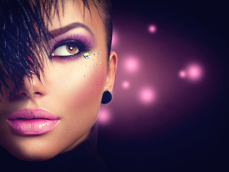 Sexy model girl face closeup with holiday bright purple makeup Stock Photo
