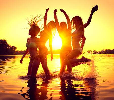 adolescente: Fiesta en la playa. Grupo de muchachas felices bailando en el agua en el hermoso atardecer de verano