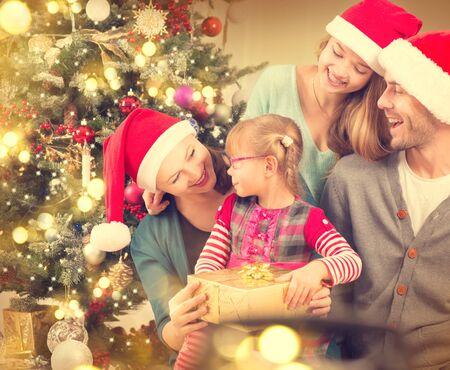 huge christmas tree: Happy smiling family at home celebrating Christmas