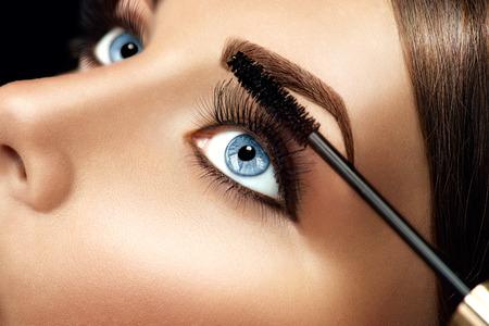 mujer maquillandose: Maquillaje que aplica el rimel primer. Pestañas extensiones Foto de archivo