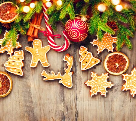 gingerbread cookies: Christmas holiday border with gingerbread cookies, candy cane over wooden background