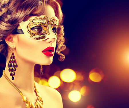gold facial: Beauty model woman wearing venetian masquerade carnival mask at party
