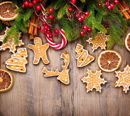galletas: Frontera de vacaciones de Navidad con galletas de jengibre, bastón de caramelo sobre fondo de madera