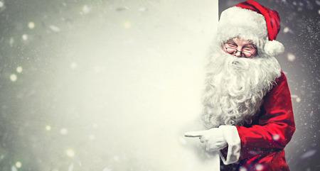 Sourire Père Noël pointant sur blanc bannière publicitaire fond avec copie espace