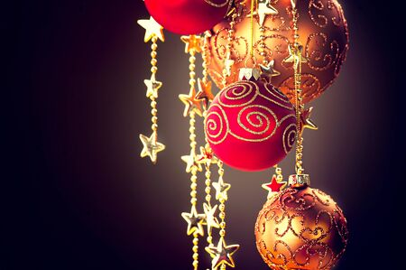 xmass: Hanging Christmas baubles and garland over dark background Stock Photo