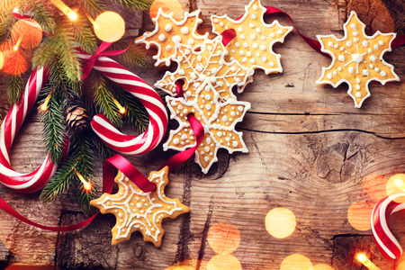 candy border: Christmas holiday background with various gingerbread cookies, candy cane and evergreens border over wooden table Stock Photo