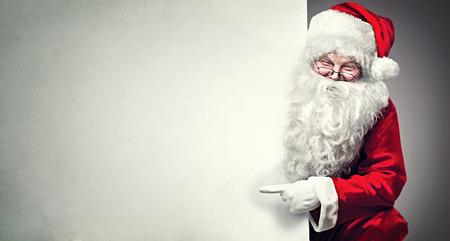 Lachende Santa Claus wijzend op lege reclame banner achtergrond met kopie ruimte