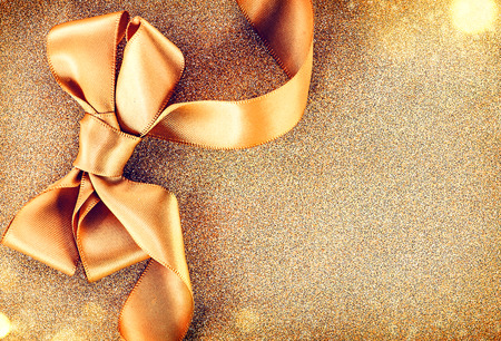 golden border: Christmas golden satin ribbon bow on a blinking holiday background Stock Photo
