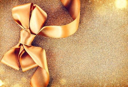 dorado: Navidad satén de oro de la cinta arco sobre un fondo de vacaciones parpadear
