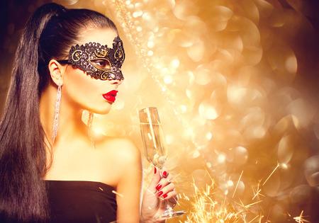 파티에서 베네치아 가면 무도회 마스크를 착용하는 샴페인의 유리 섹시 모델 여자 스톡 콘텐츠