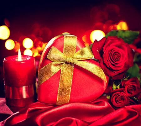 saint valentine   s day: Valentine gift box and rose flower on red silk background