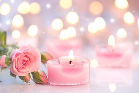バレンタインの日。ピンクのハート形のキャンドルとばら色の花