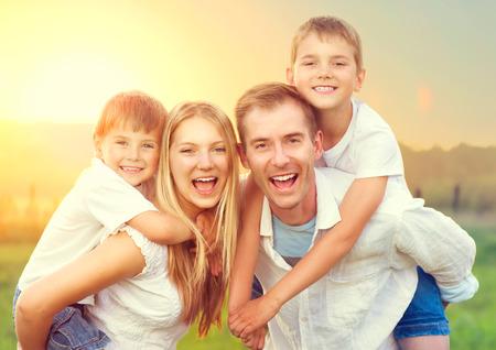 Familia joven feliz con dos niños en el campo de verano de trigo