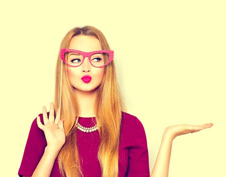 Beauté fille avec des lunettes de papier sur le bâton montrant copie espace vide sur la main ouverte Banque d'images
