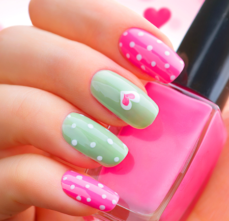 pink nail polish: Valentines Day holiday style bright manicure with painted hearts and polka dots
