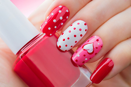 nail polish bottle: Valentines Day holiday style bright manicure with painted hearts and polka dots