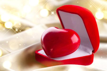 Valentine heart in gift box on golden silk background