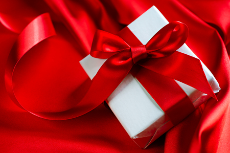 saint valentine   s day: Valentine gift box with red satin ribbon on red silk background