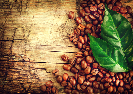 Coffee beans over wood background