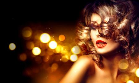 Piękna kobieta z pięknym makijażu i kręcone fryzury na wakacje ciemnym tle