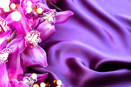satiny: Elegant violet silk and orchid flowers background