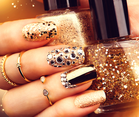 nail polish bottle: Golden holiday style bright manicure with gems and sparkles. Trendy accessories