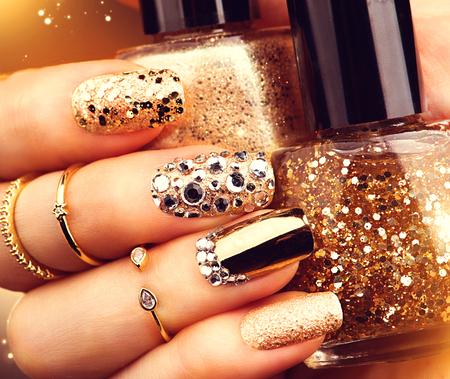 le style de vacances d'or manucure lumineux avec des pierres précieuses et des étincelles. accessoires branchés Banque d'images